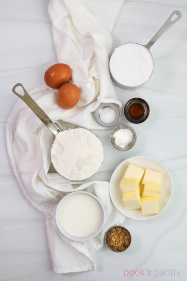 Ingredients for ginger cupcakes on white marble background.