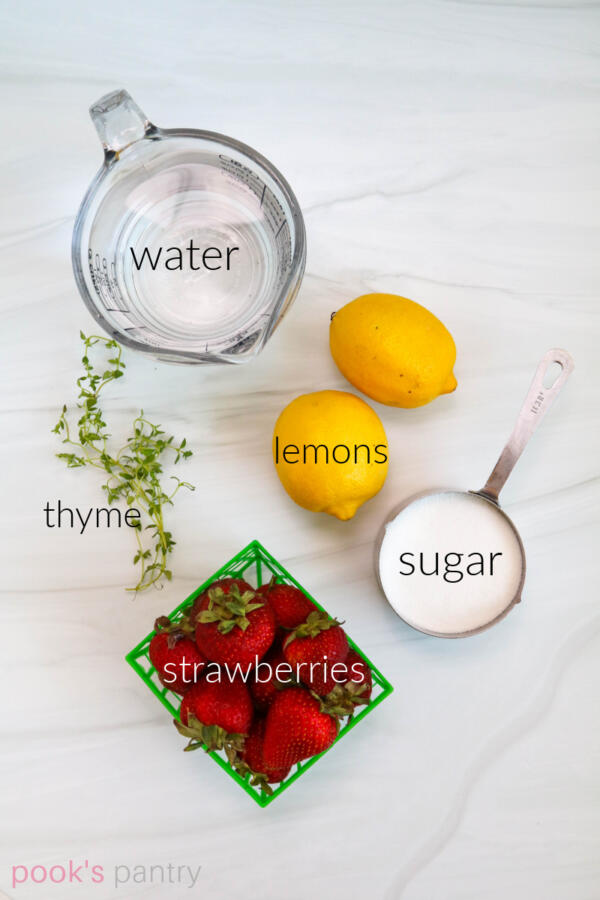 Ingredients for strawberry thyme lemonade on marble background.