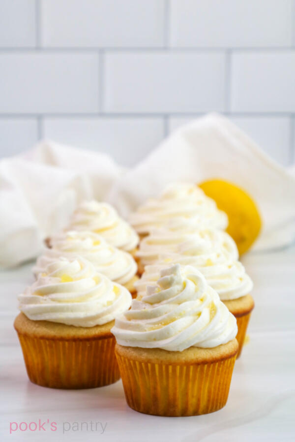 Lemon ginger cupcakes lined up in two rows on marble background.