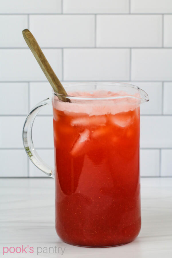 Pitcher of pink lemonade with wooden spoon on white background.