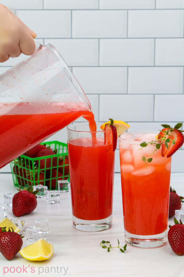 Pouring strawberry herbal lemonade into tall, clear glasses with whole strawberries and lemon wedges scattered around the counter.