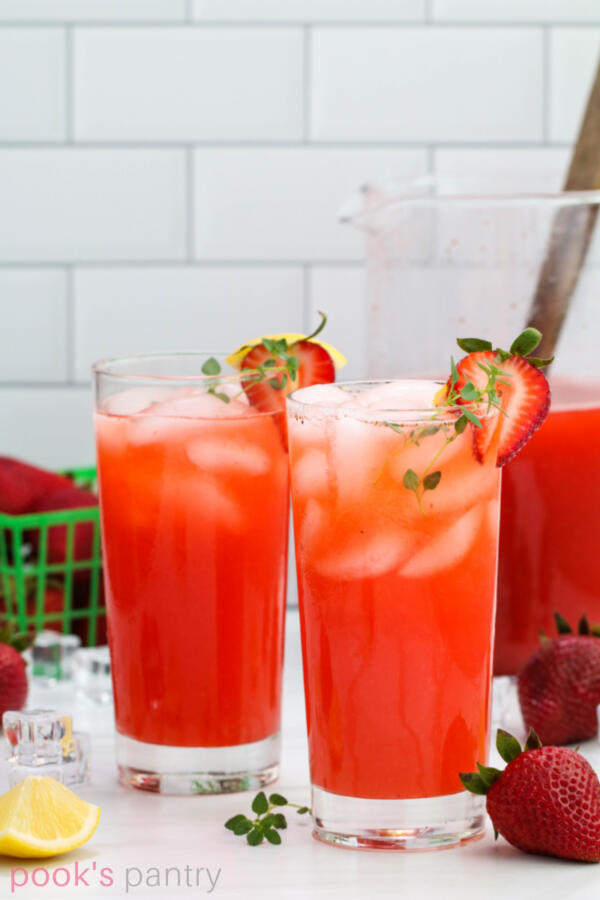 Glasses of strawberry thyme lemonade garnished with sliced strawberries and lemons on white marble background.