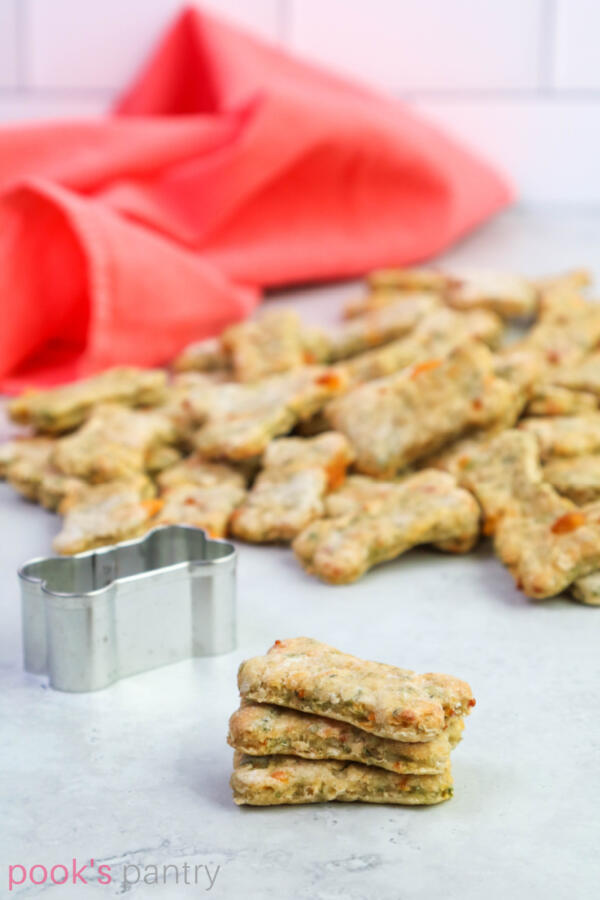 Dog treats with apples and cheese on marble background with coral colored napkin in background.