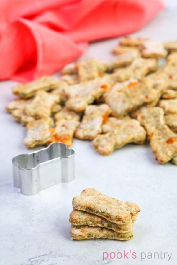 Cookies with oatmeal and apples for dogs in a stack of 3 with a pile of treats in the background.
