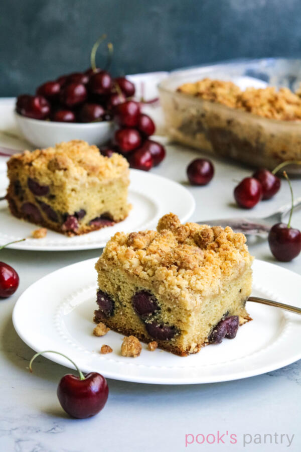 Slice of cherry crumb cake with crumb topping on round, white plate. Cherries in background with silver cake server.