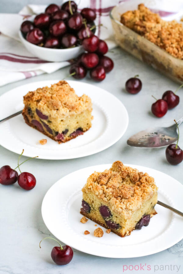 Squares of crumb cake on white plates with cherries scattered around. Crumb cake with silver cake server in the background.