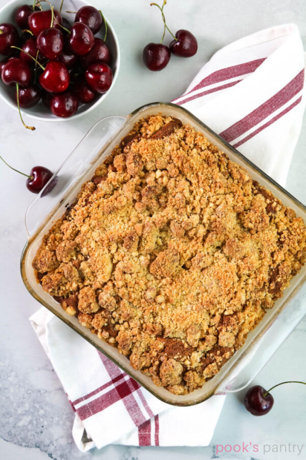 Overhead photo of crumb cake in glass baking pan on white and red towel.