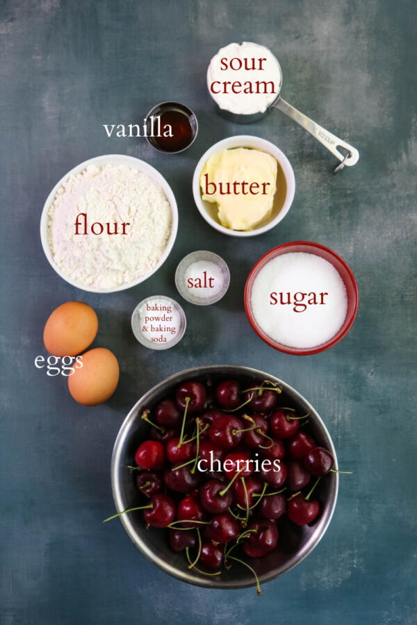 Ingredients for cherry crumb cake on grayish-blue background.