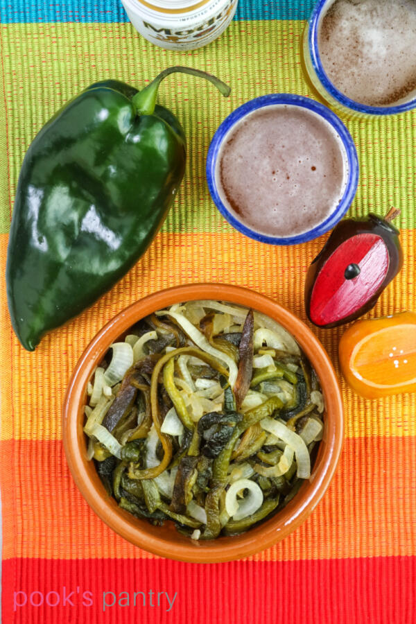 Vegan rajas recipe in terra cotta dish with poblano pepper on the side.