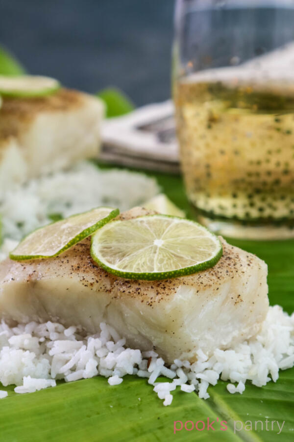 Corvina fish sitting on a bed of rice on top of a banana leaf with limes on top.