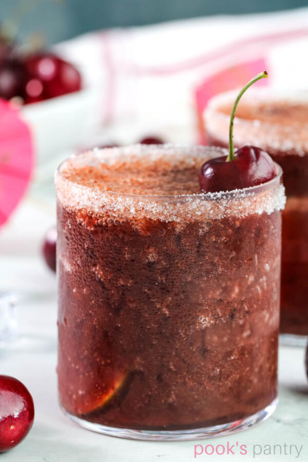 Fresh cherry daiquiri in short, clear glass with Bing cherry garnish.