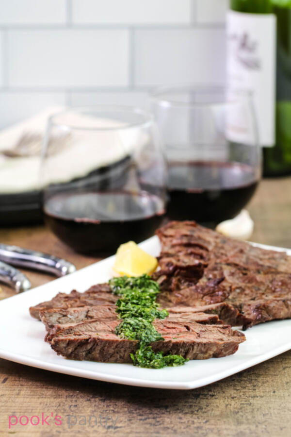 Steak gremolata on white platter with wine glasses in the background on a wood butcher block.