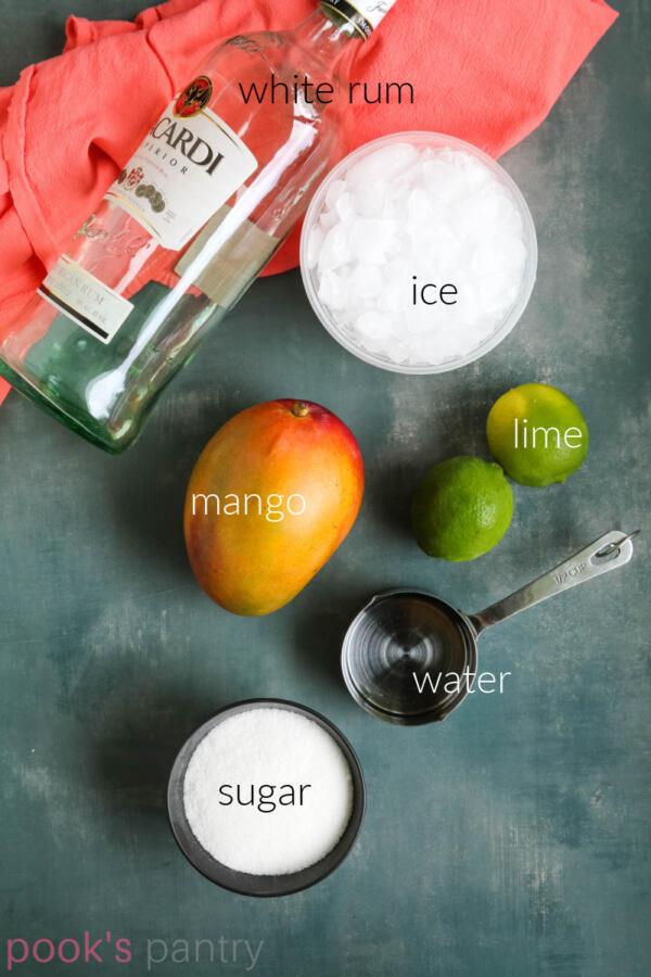 Recipe ingredients for mango daiquiris on gray background.