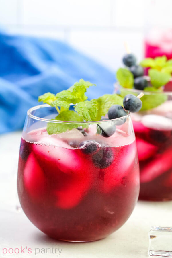 Small clear glass filled with blueberry lemonade and ice. Garnished with fresh blueberries and mint.