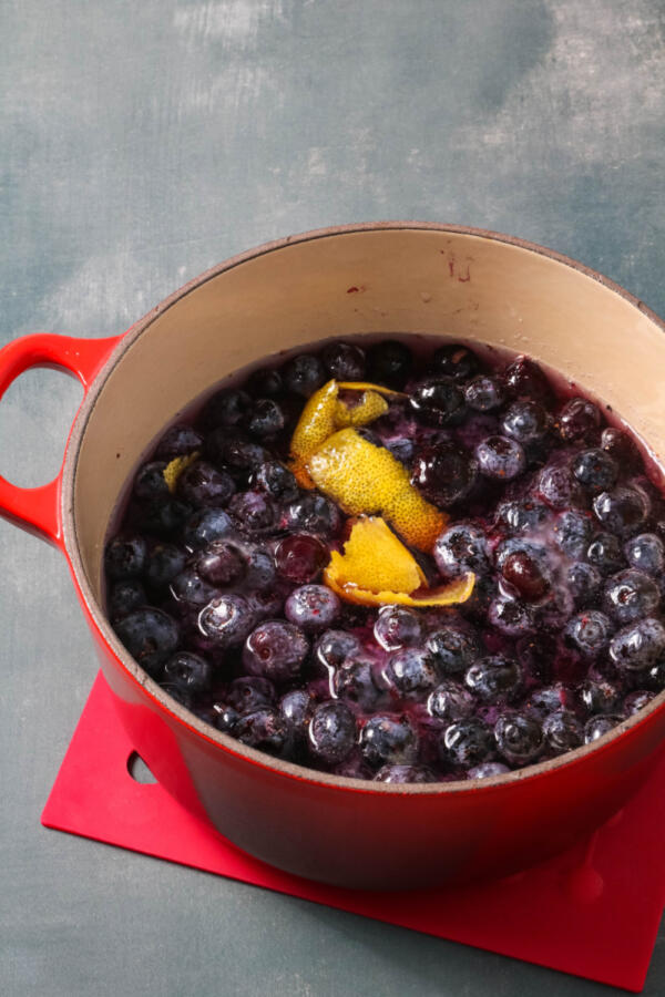 Making blueberry syrup for lemonade recipe in small red pot.