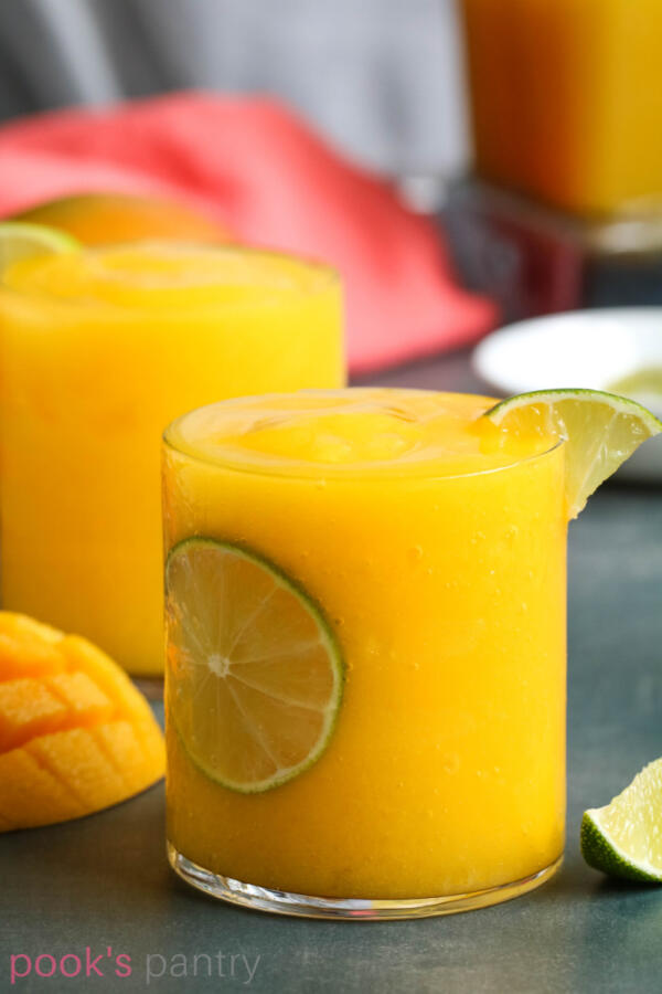 Fresh mango daiquiris in short clear glasses with lime garnish.