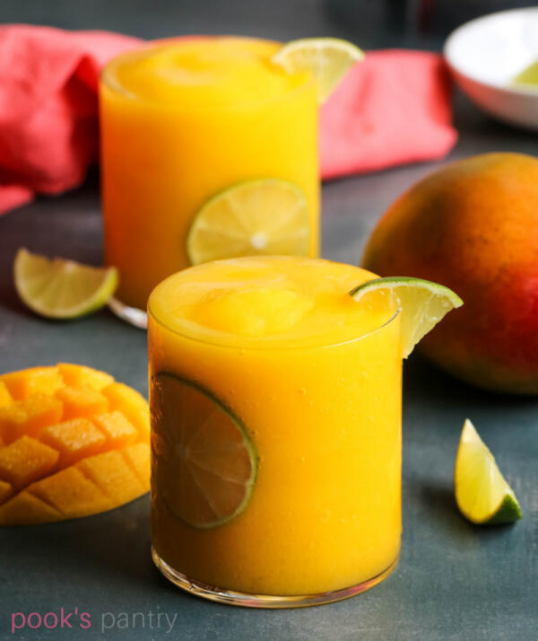 Easy mango daiquiri recipe in clear glass with mangoes and lime in background.