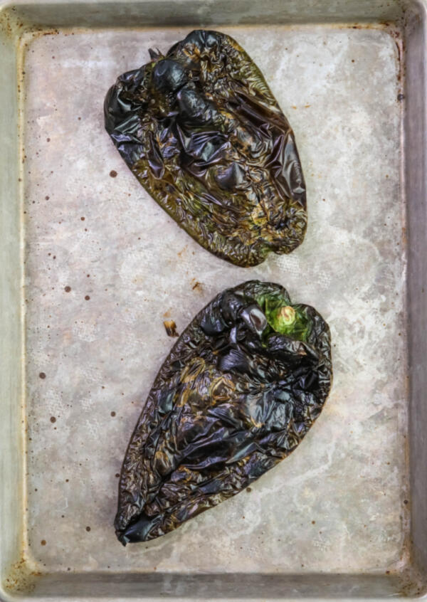 Roasted poblano peppers for rajas on a baking sheet.