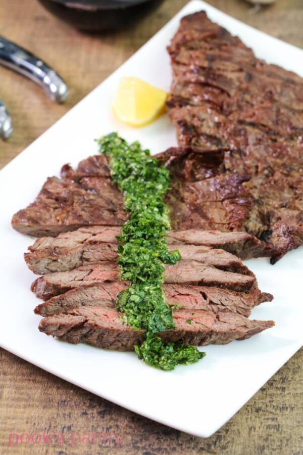 Steak gremolata on white rectangular platter with lemon wedges.