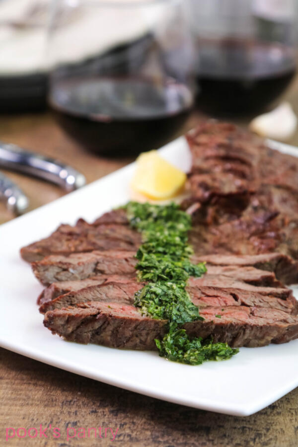 Grilled steak on white platter with green gremolata sauce drizzled on top.
