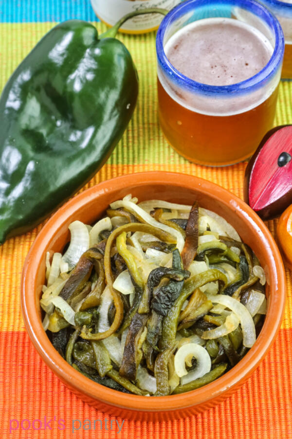 Vegan rajas recipe in shallow terra cotta bowl with glass of beer above dish.