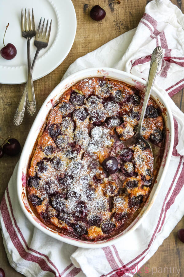 Cherry clafoutis recipe with red and white kitchen towel and white plates in the background.