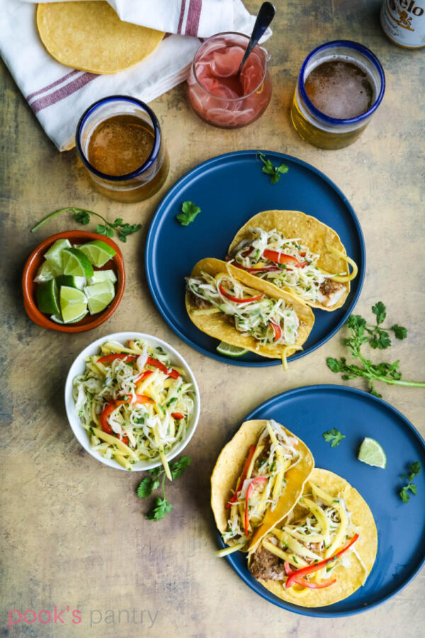 Corvina tacos on blue plates with cilantro and lime.