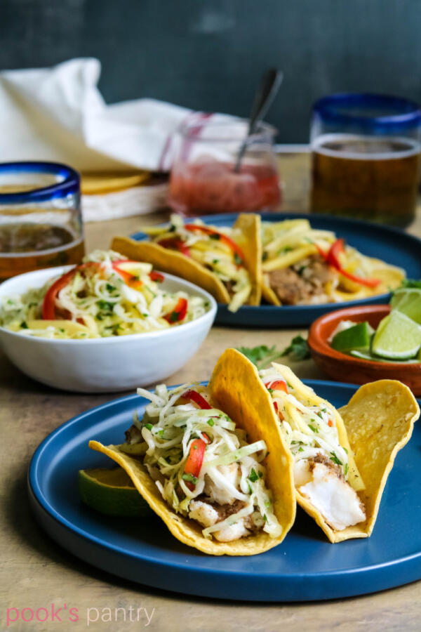 Corvina tacos with mango slaw on blue plate with limes and beer in background.