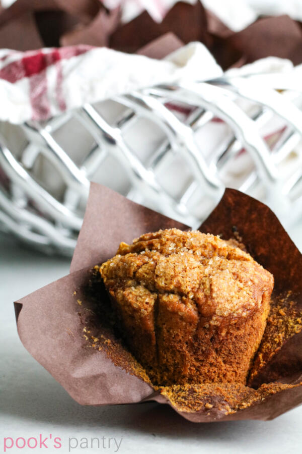Pumpkin applesauce muffin in brown tulip muffin paper in front of silver basket.