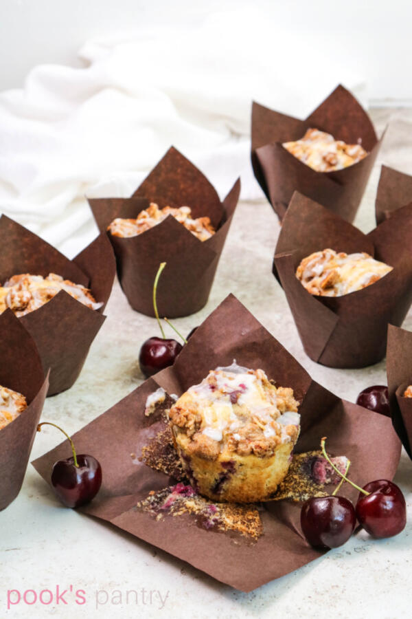Muffins in paper liners with cherries and almonds on tan background.