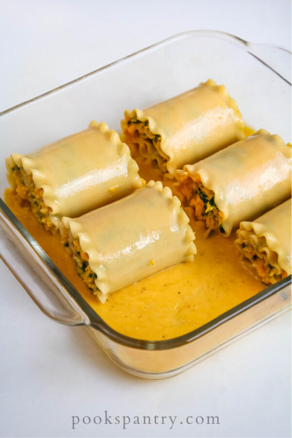 Squash lasagna rolls in glass baking dish on a white background.