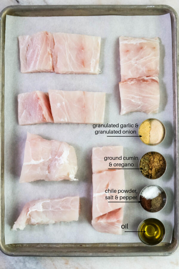 Portions of corvina for tacos with spices on baking sheet.