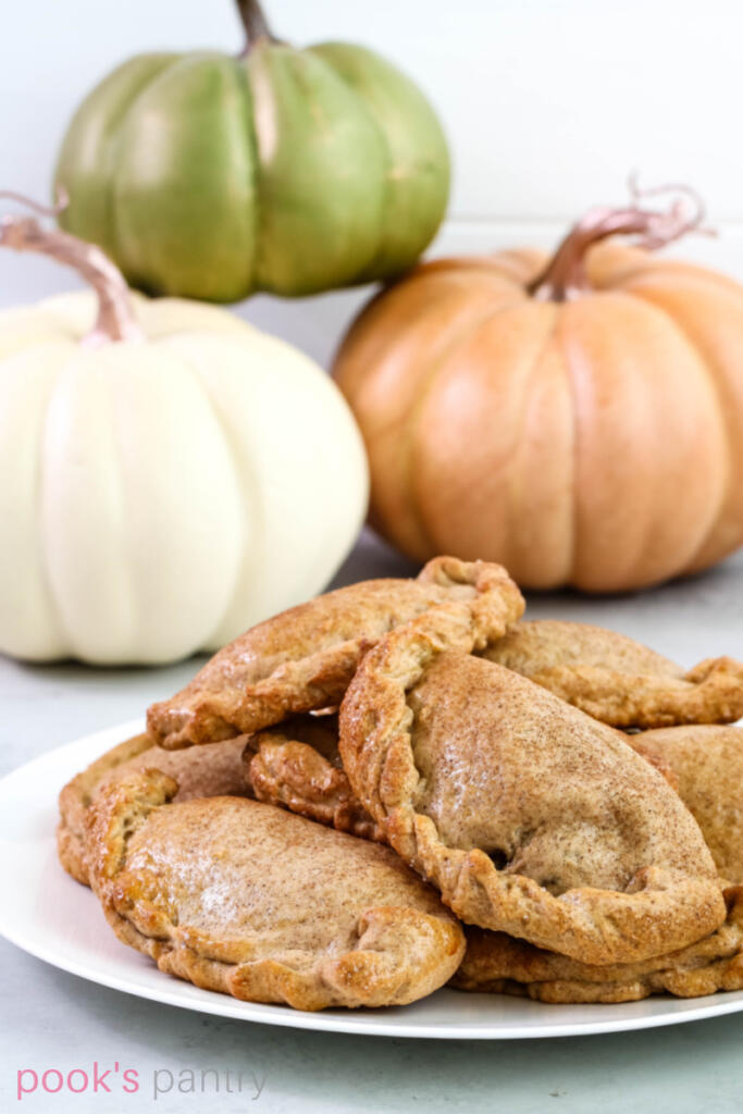 Pumpkin empanadas from scratch on a large white plate with decorative pumpkins in the background.