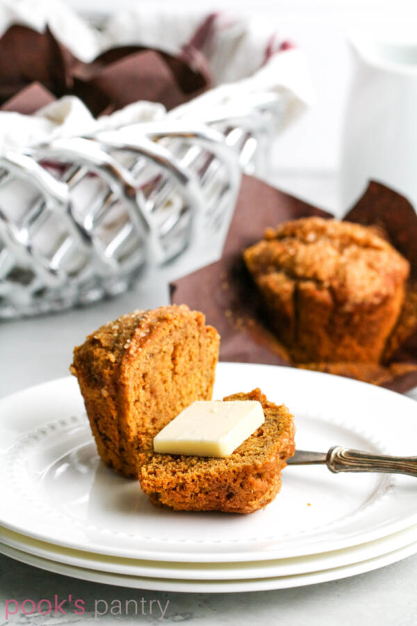 Pumpkin applesauce muffin with butter on stacked white plates with antique butter spreader.