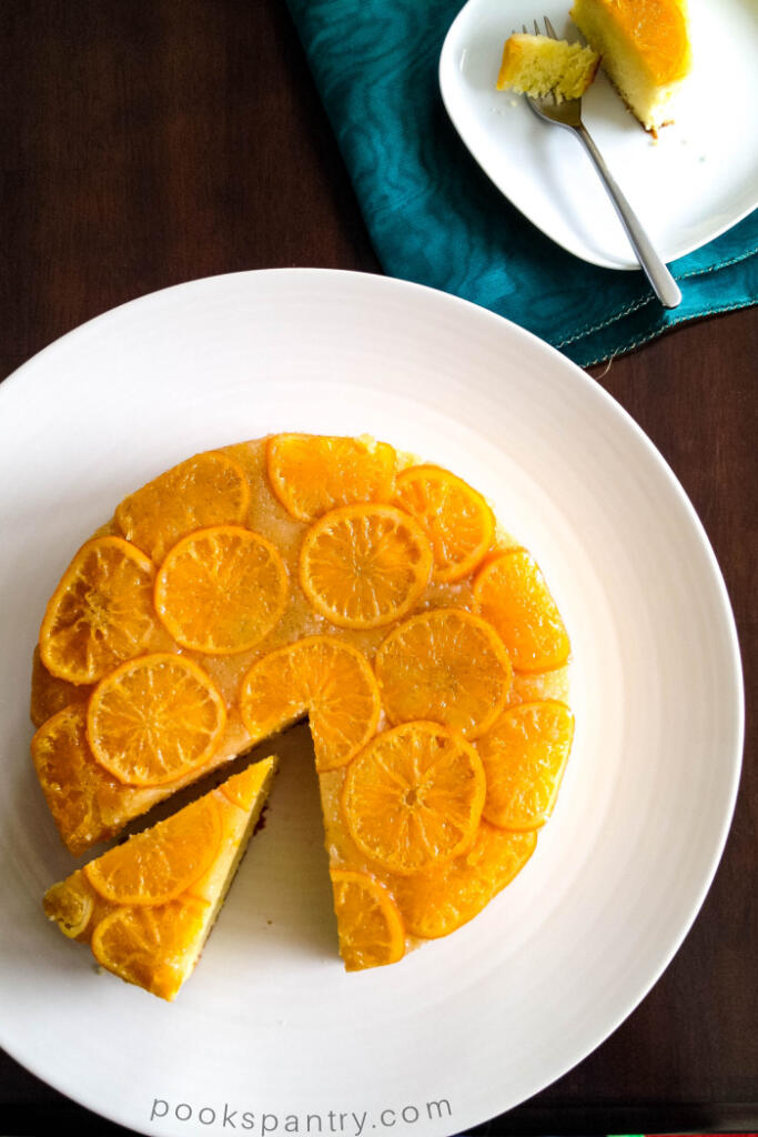 Clementine upside down cake on white platter with slice of cake on a small square plate on teal napkin in the background.