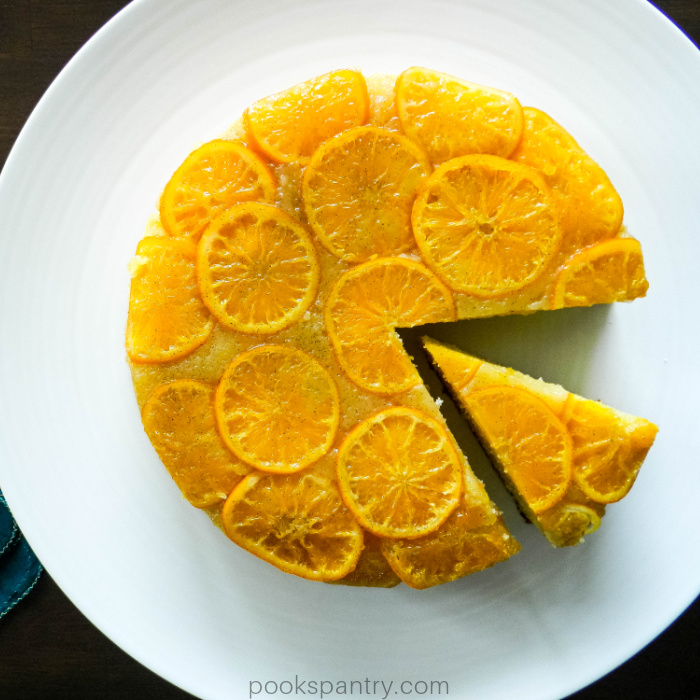 Upside down clementine cake on large white platter.