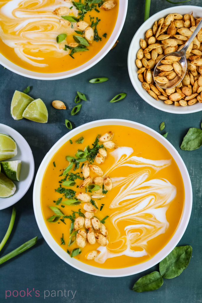 Curried squash soup with coconut milk with herb garnish and roasted pumpkin seeds.