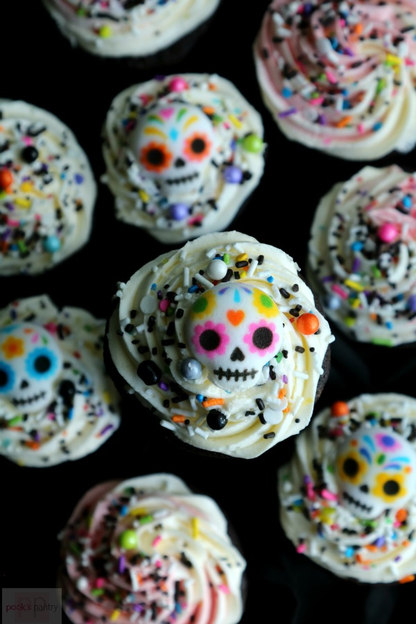 Day of the dead desserts with sugar skull decorations and sprinkles.