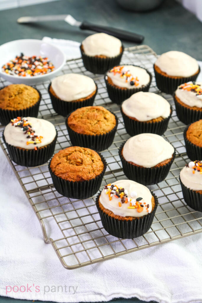 Hubbard squash muffins with vanilla glaze and sprinkles on a cooling rack with a white towel underneath.
