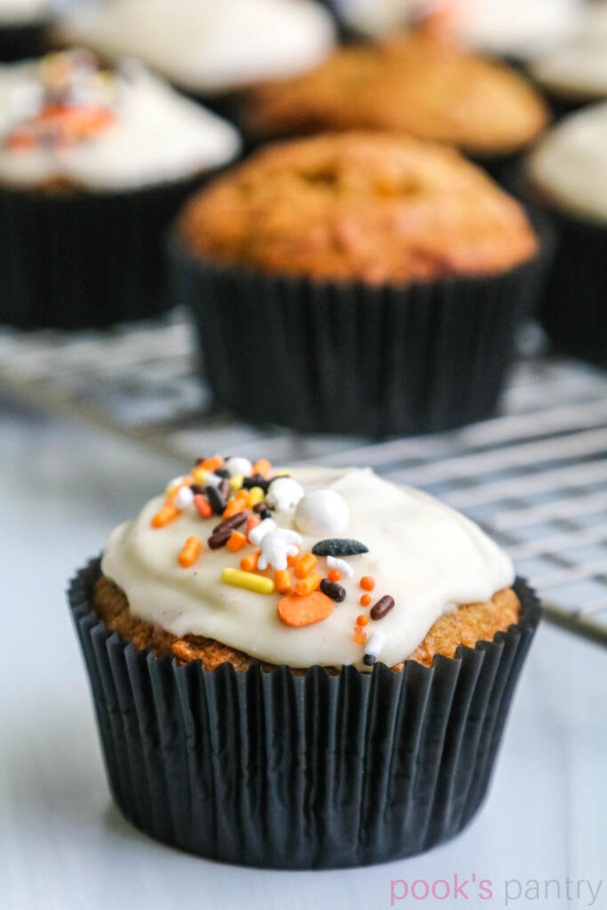 Squash muffins with maple glaze and sprinkles in black muffin paper with muffins on cooling rack in the background.