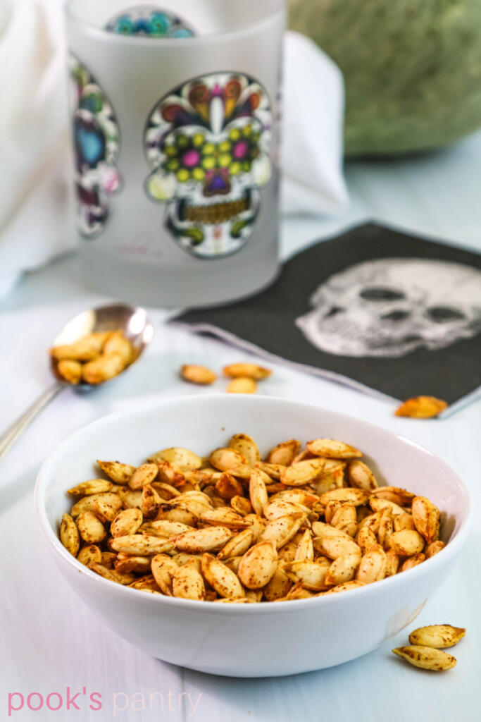 Roasted Hubbard squash seeds in white bowl with colorful glass in the background.