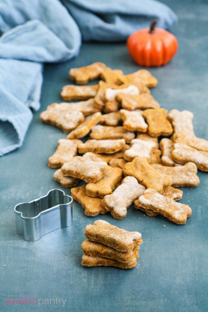 Pumpkin dog treats with carrots stacked on a blue background, with a pile of treats behind them.