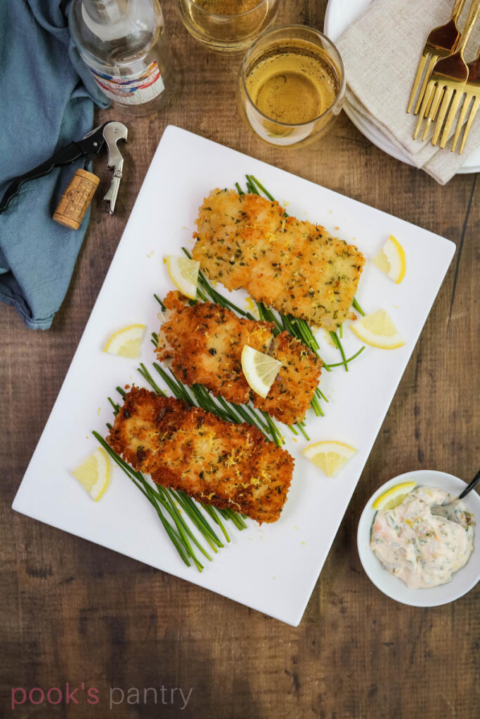 Breaded corvina filets on platter with homemade tartar sauce in a small bowl on the side.