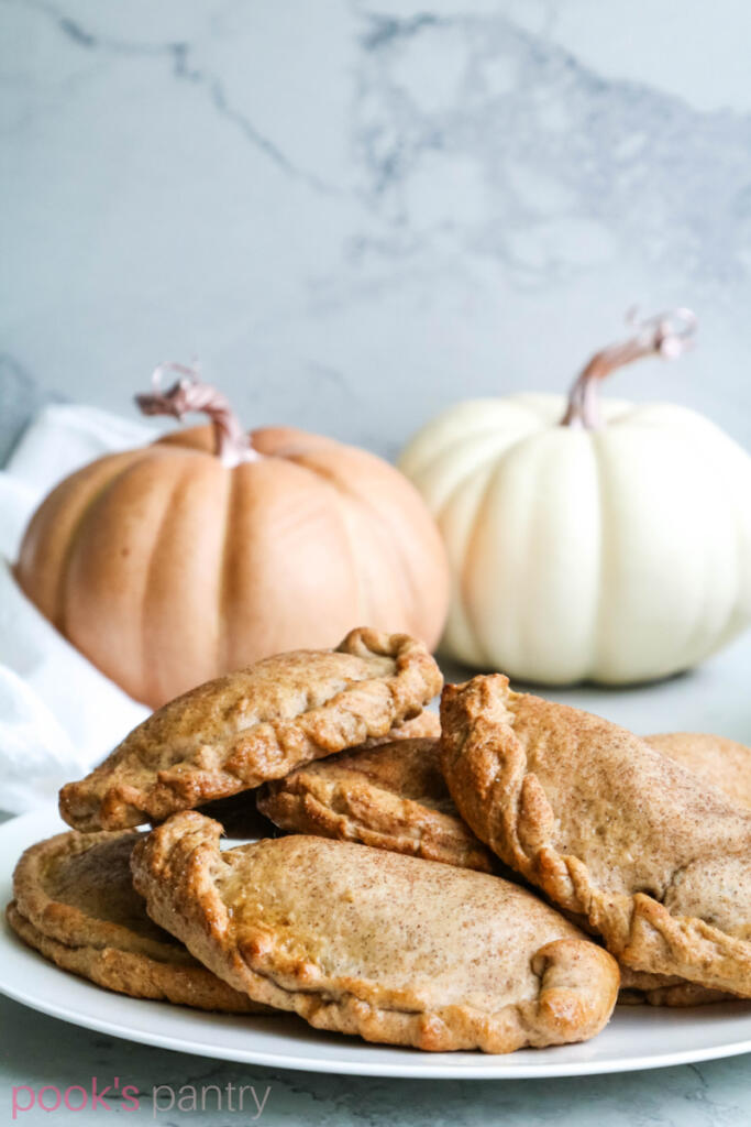 Pumpkin empanadas on white plate on gray marble backdrop with pumpkins in the background.