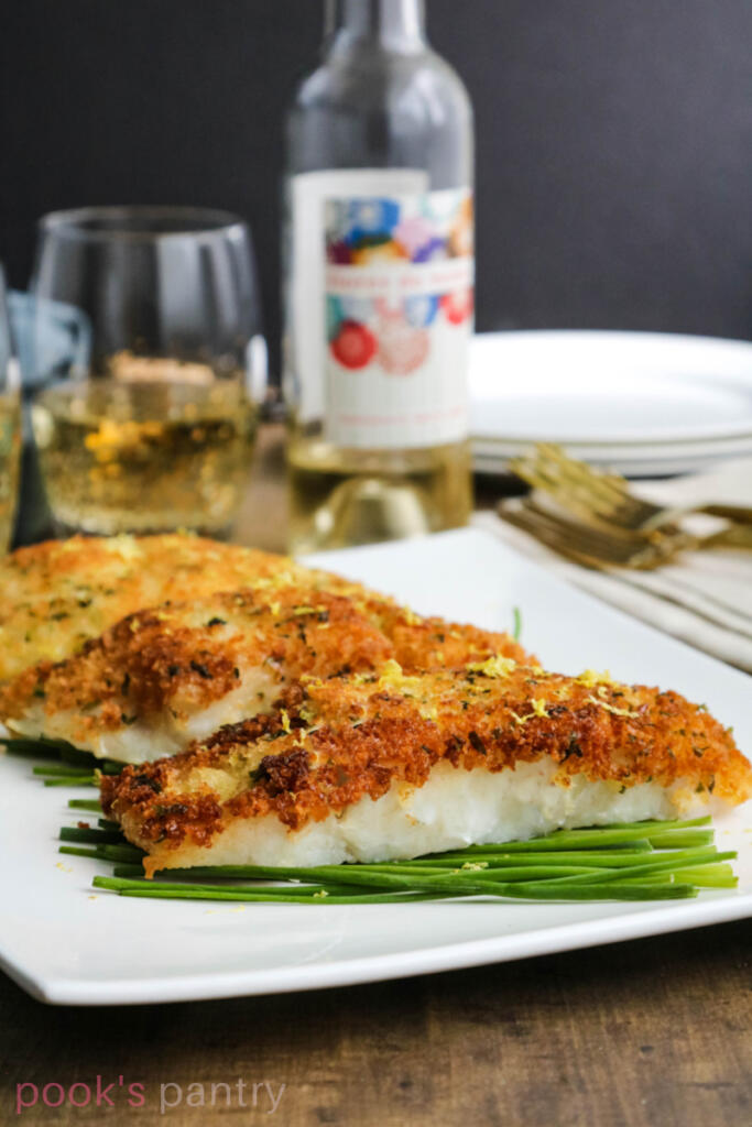 Pan fried corvina on white platter with glasses of wine in the background.
