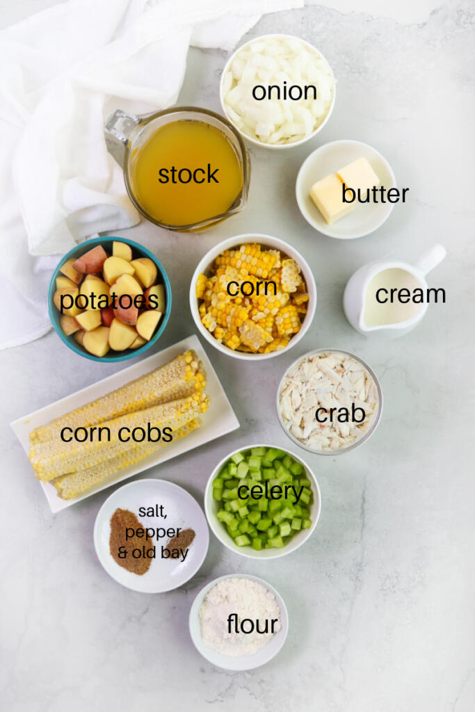 Ingredients for crab and corn chowder on gray marble background.