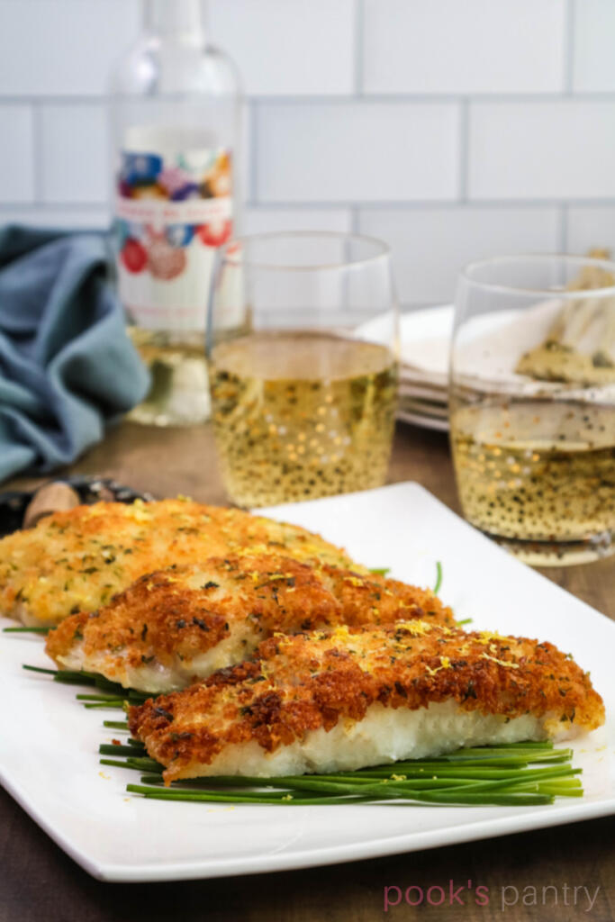 Pan fried corvina on bed on chives on a white platter. Wine glasses and bottle in the background.