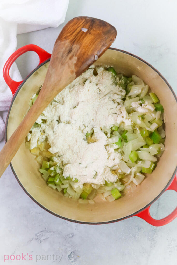 Roux with celery and onions in red Dutch oven pot.