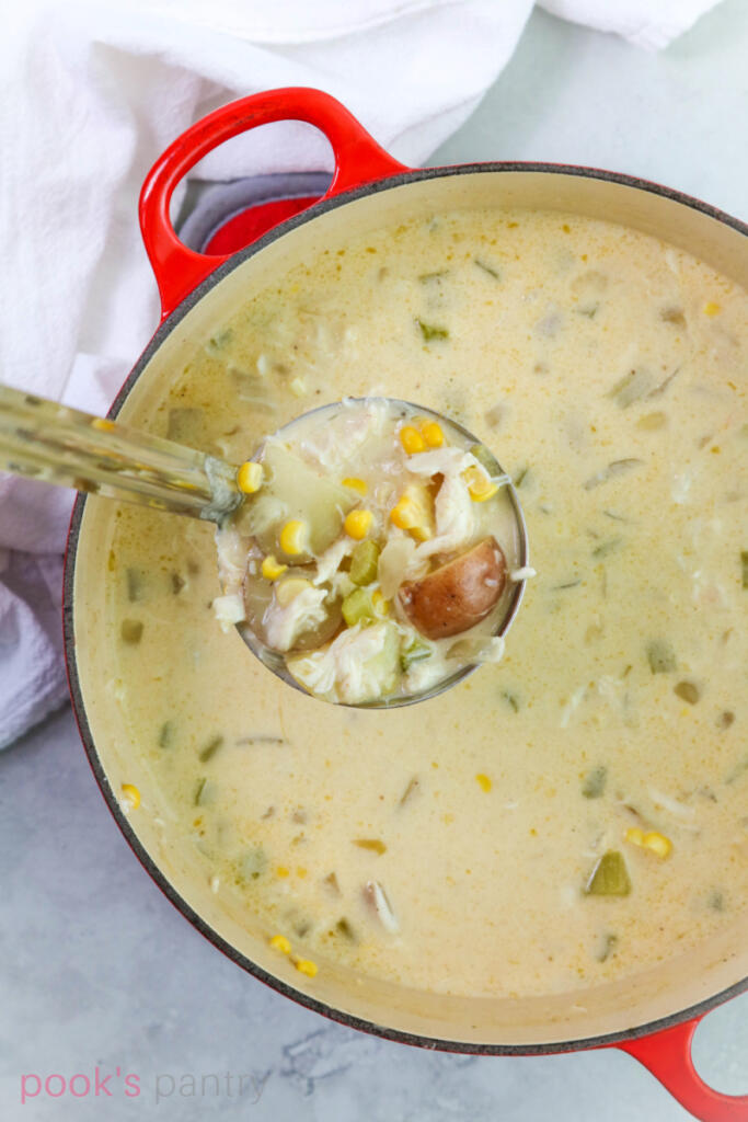 Ladle full of crab and corn chowder with pot of chowder underneath.