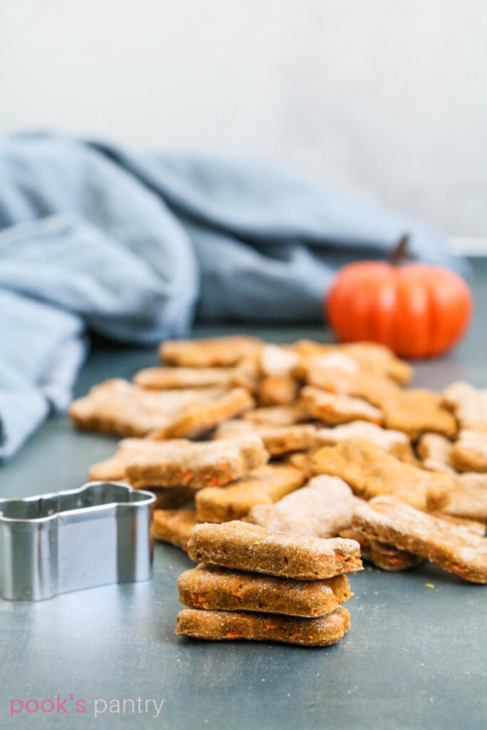 Three dog treats stack on top of one another with bone shaped cutter to the side.